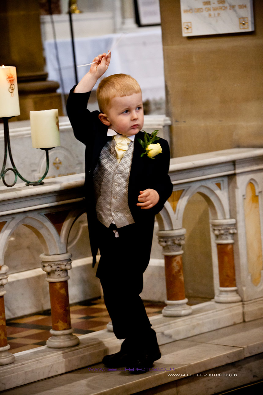 page boy playing with church candles during wedding ceremony