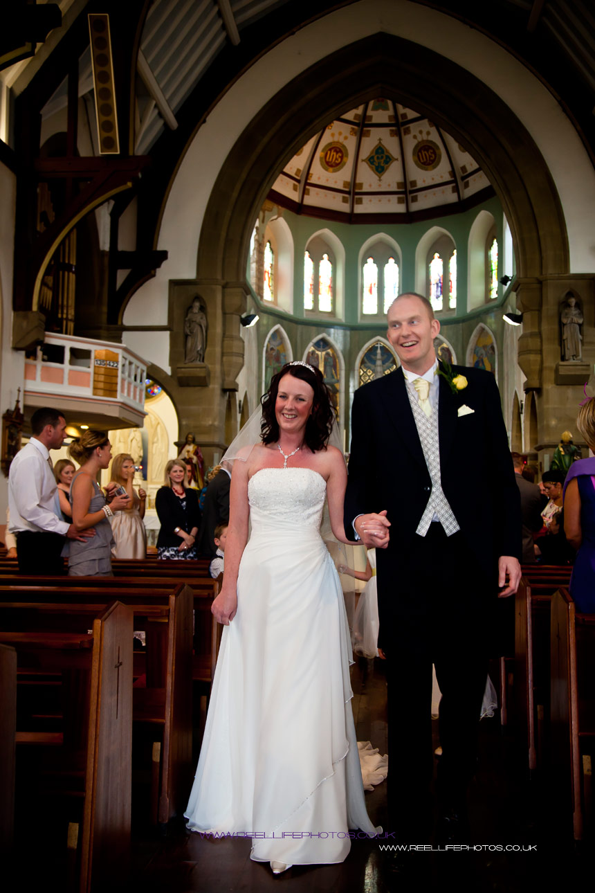 happy bride and  groom walking down the aisle of st marys church in batley