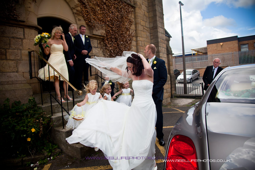wedding party leaving church with the wind catching the bride's veil