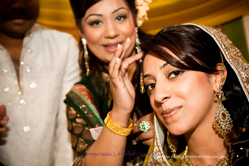 Asian wedding photography: Oil is rubbed onto the bride's hair as part of the Mehndi ritual