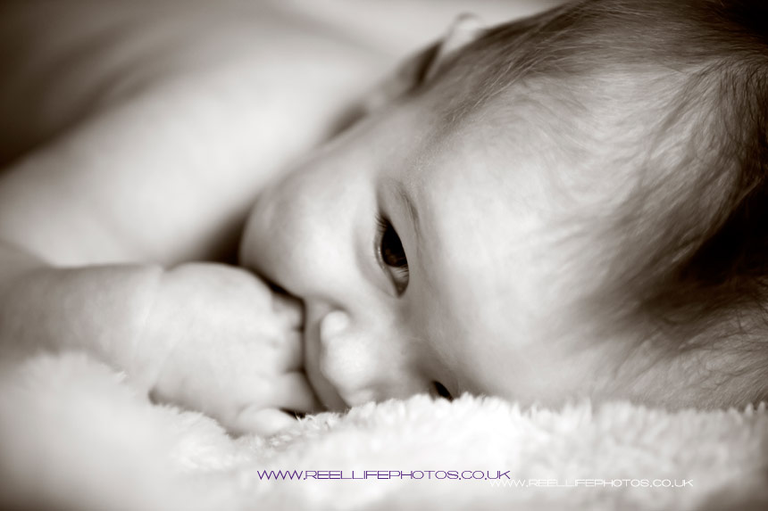 Baby in Sepia - lying on a fleece chewing his hands.