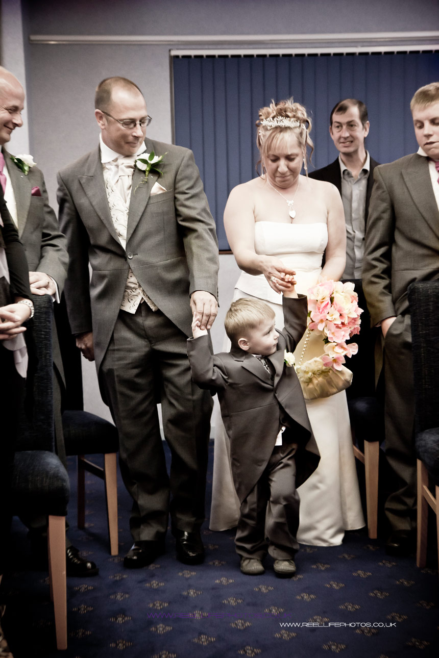 bride and groom walking down the aisle with their grandson