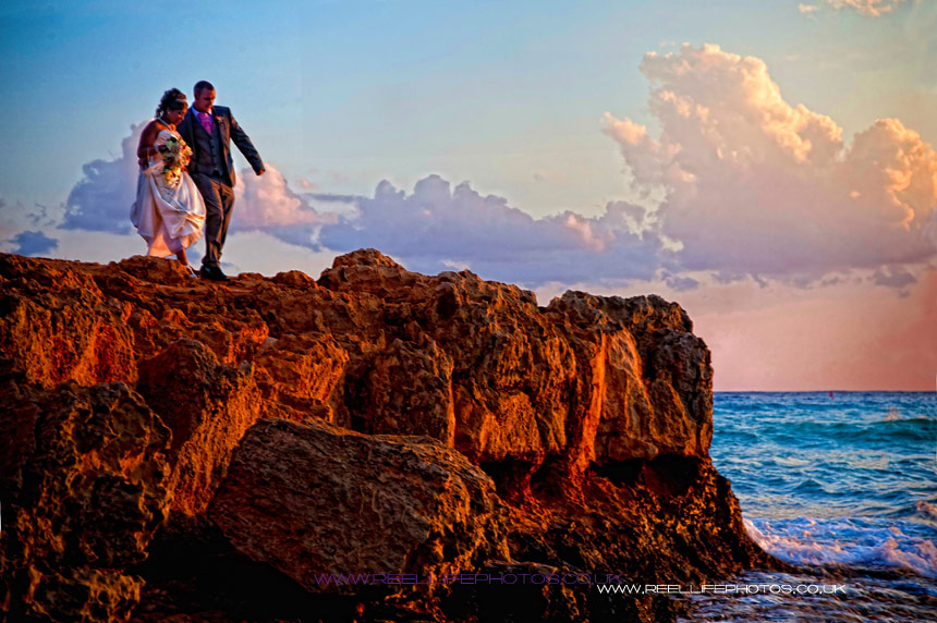Bride and Groom on rocky outcrop at sunset at Nissi Beach in Cyprus
