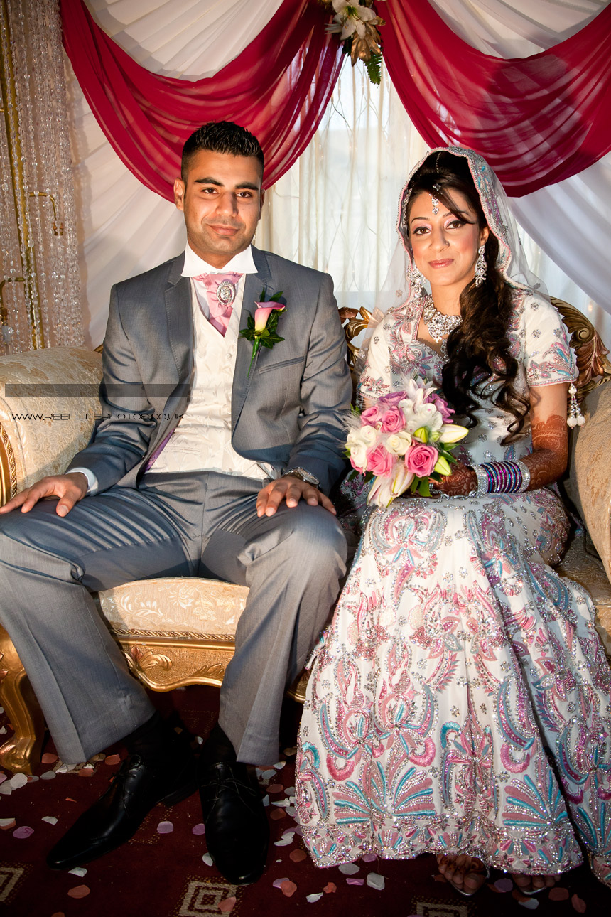 Full length photo of seated Asian bride and groom