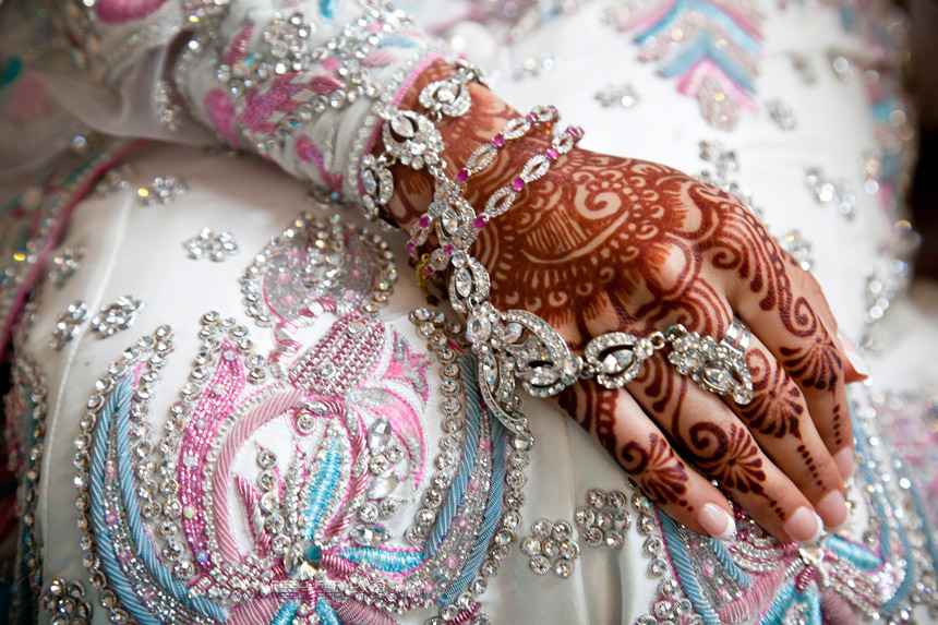Detail of Asian bride's bejwelled  hand on her wedding dress