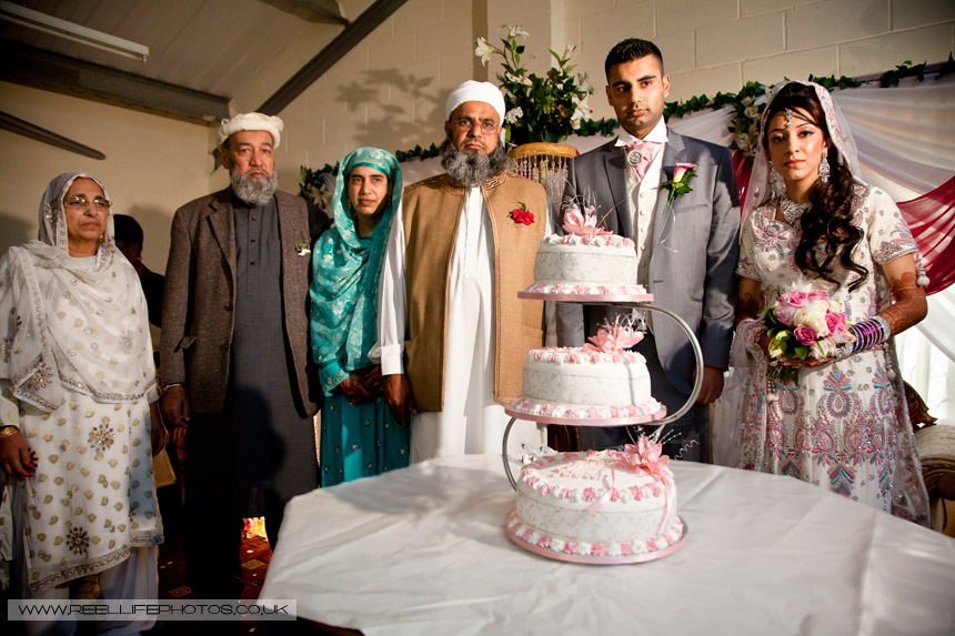 Asian wedding photo with parents, bride and groom by cake