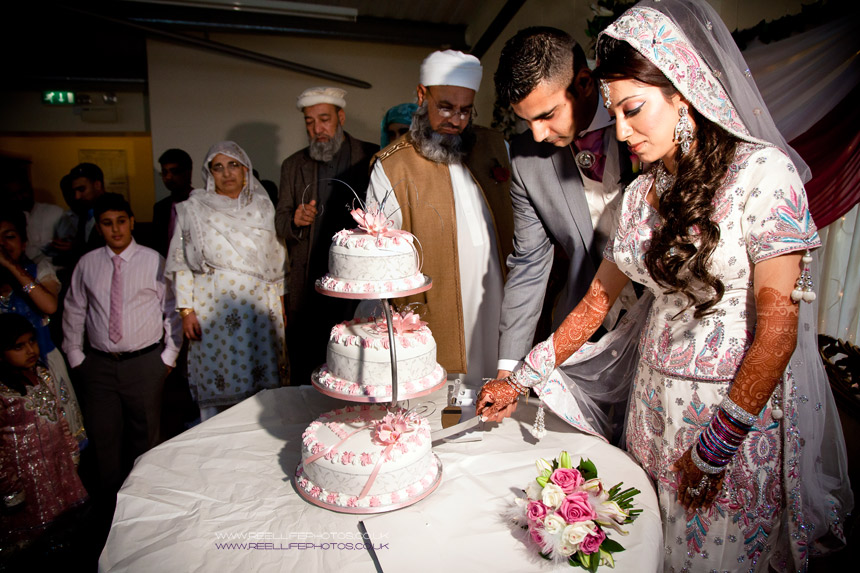 Asian bride and groom cutting the cake
