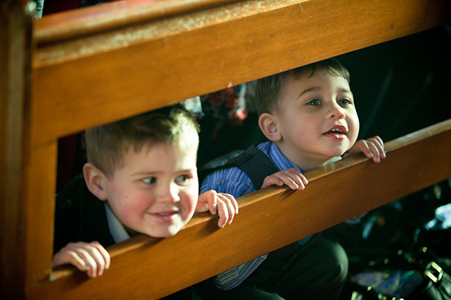 Little boys peeping out of pews during Christening