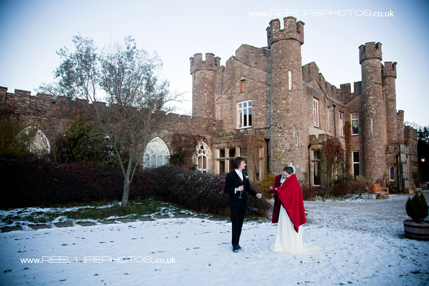 Bride and Groom outside in the snow at Augill Castle in Cumbria