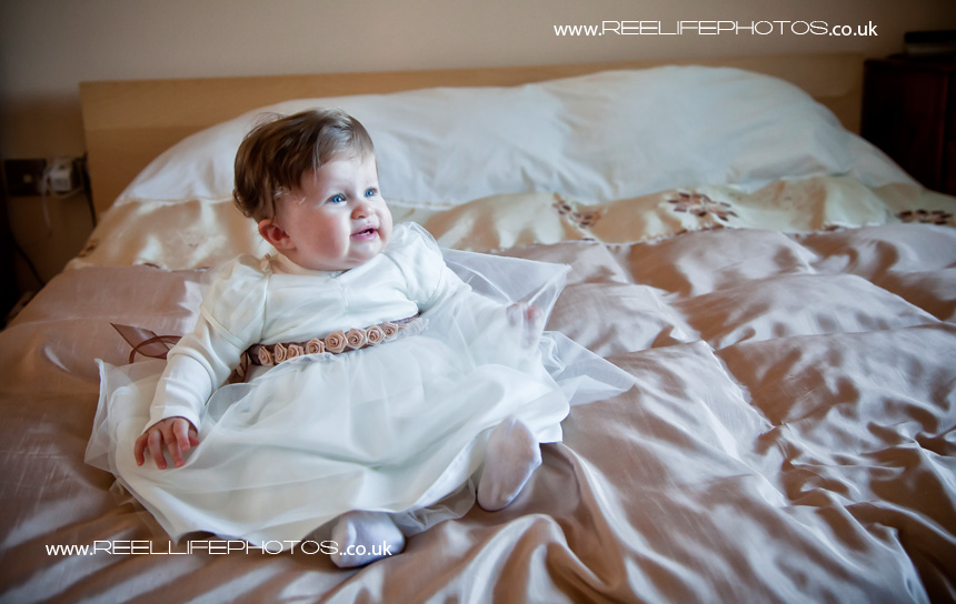 bride and groom's baby daughter in her wedding outfit