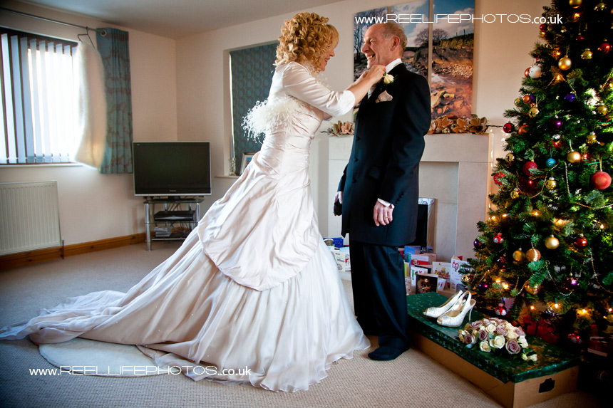 Winter bride sorting out her Dad's cravat on her wedding day