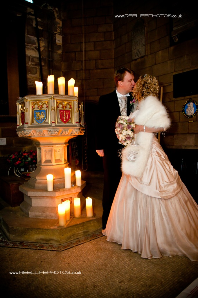 bride and groom in church by the font