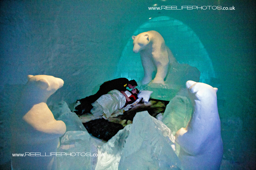 Groom kisses bride in polar bear room a the  Ice Hotel