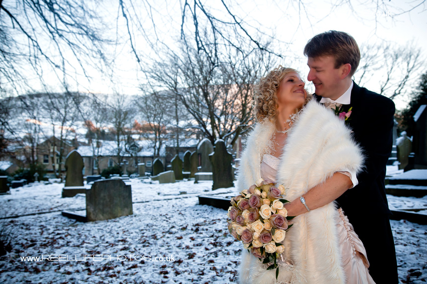 Romantic pic of bride and groom outside the church in the snow