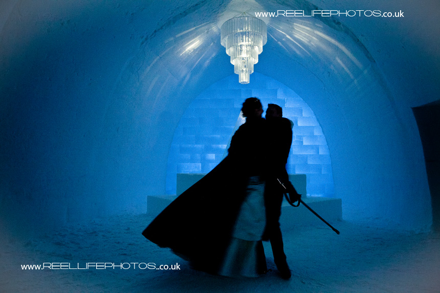 silhouette of bride on black cape being twirled around inside Ice Hotel