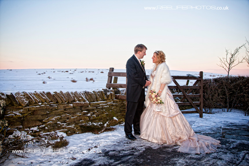 Bride and Groom in the snow atoutside the Huntsman Inn near Homefirth
