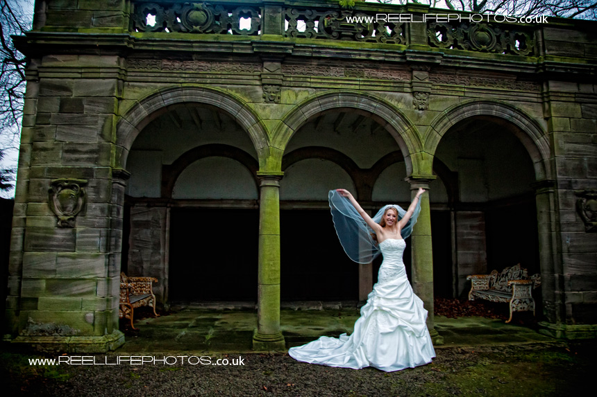 bride by arched folly at Thornton Manor