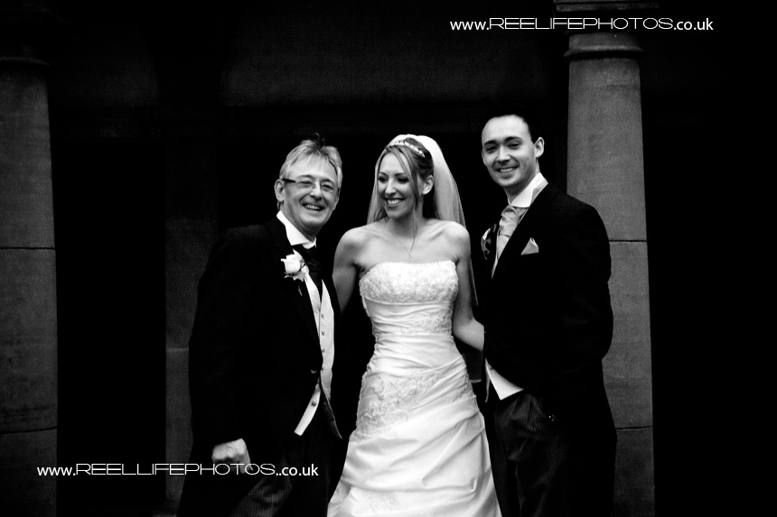 black and white wedding photo of groom with his father and new bride