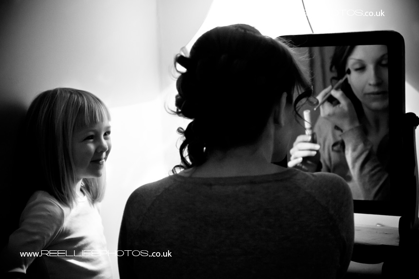 black and white wedding prep picture of little girl watching make-up