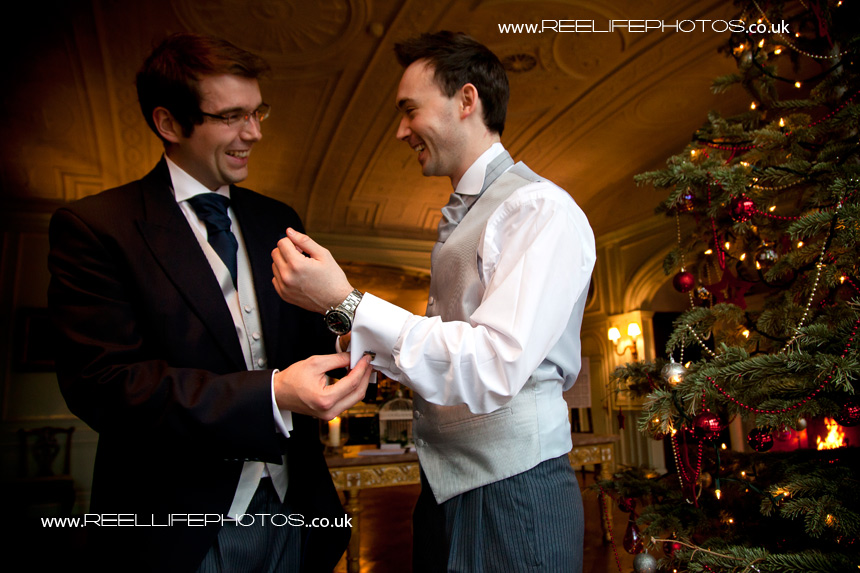 Groomsman helps groom on with his cufflinks