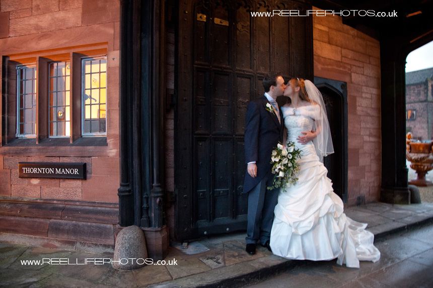 winter wedding with bride and groom outside gates of Thornton Manor