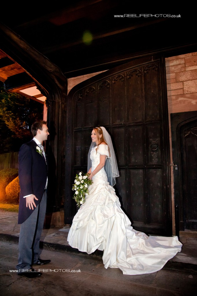 evening wedding picture of bride and groom by gates at Thornton Manor