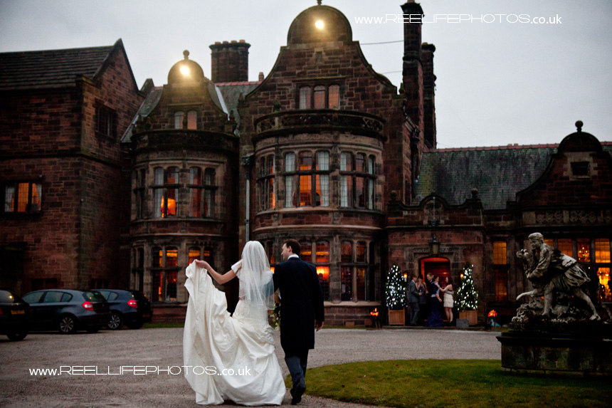 evening pic back view of bride and groom walking into Thornton Manor
