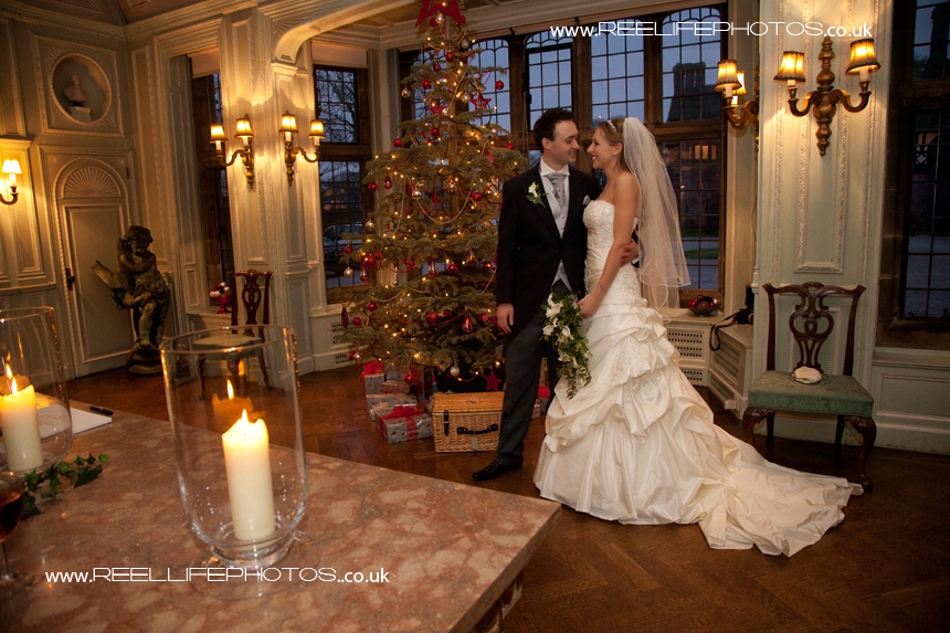Bride and groom by Christmas tree on New Year's Eve at Thornton Manor