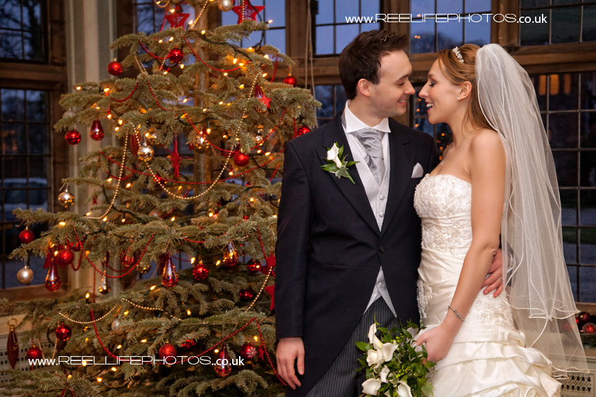 close up of bride and groom by Christmas tree