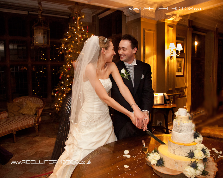 bride and groom cutting the cake at their wedding reception at Thornton Manor