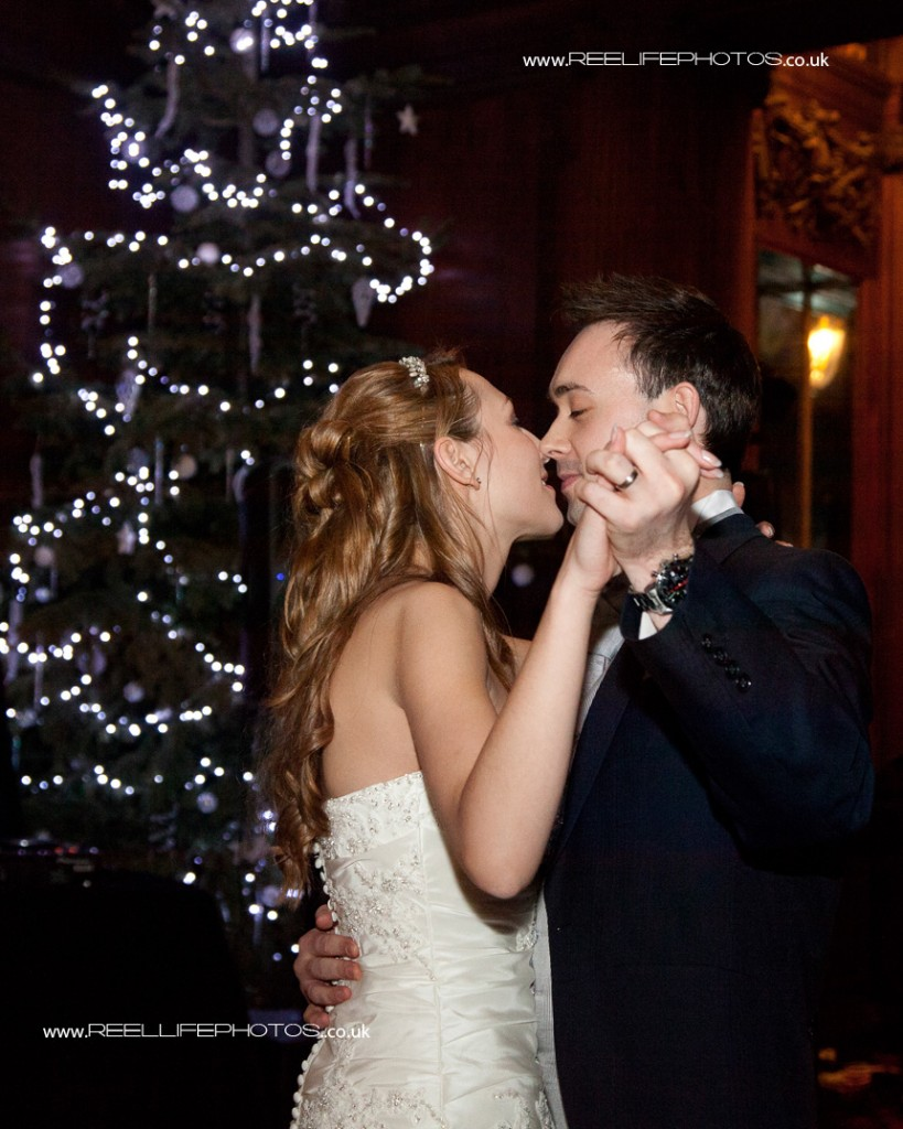 bride and groom kiss by the Christmas tree