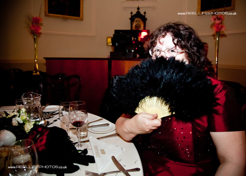 black feather fan at masked wedding ball