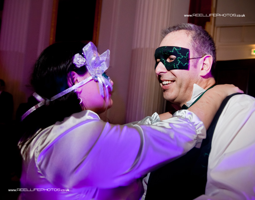 couple dancing at5 masked ball wedding reception