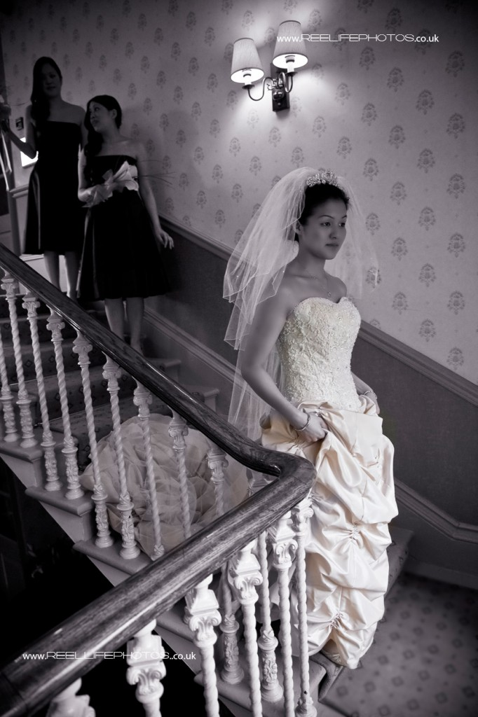 natural wedding picture of bride coming down stairs at Weetwood Hall