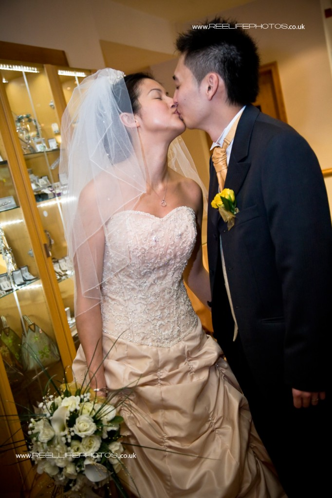 colour wedding photograph of bride and groom kissing