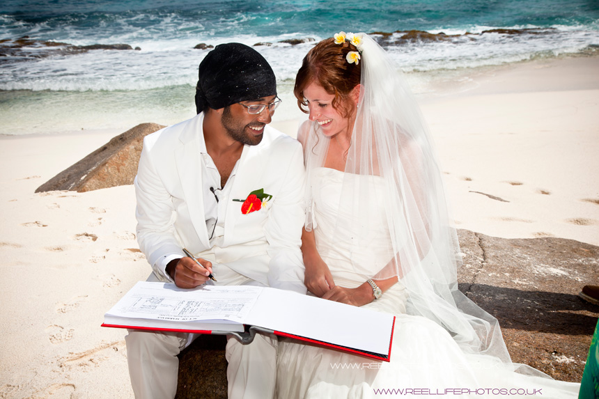 signing the  register on the beach in the Seychelles after beach wedding