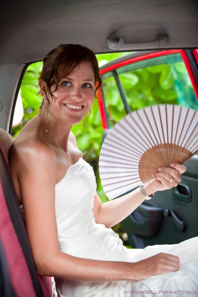 bride with fan inside Seychelles wedding car