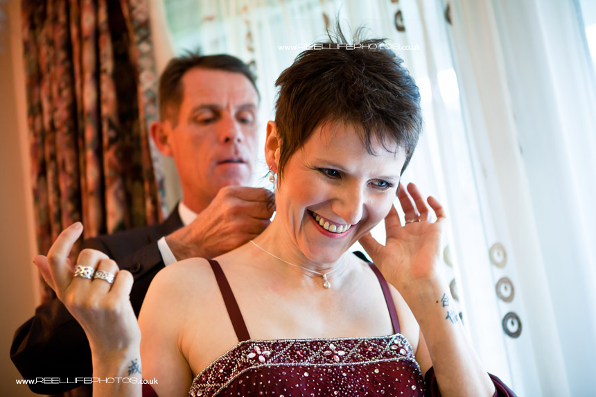 Groom puts on bride's necklace for her