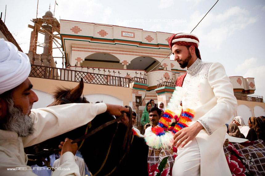 Asian groom on horseback at Pakistani wedding