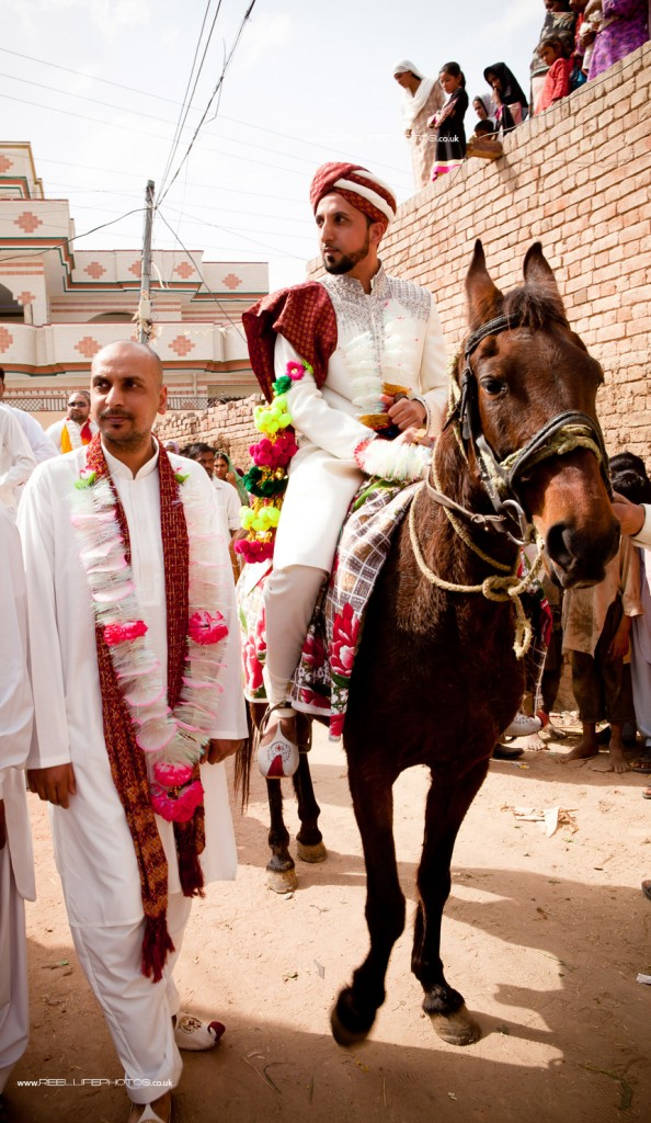 Asian groom riding to his wedding in Pakistan on horseback