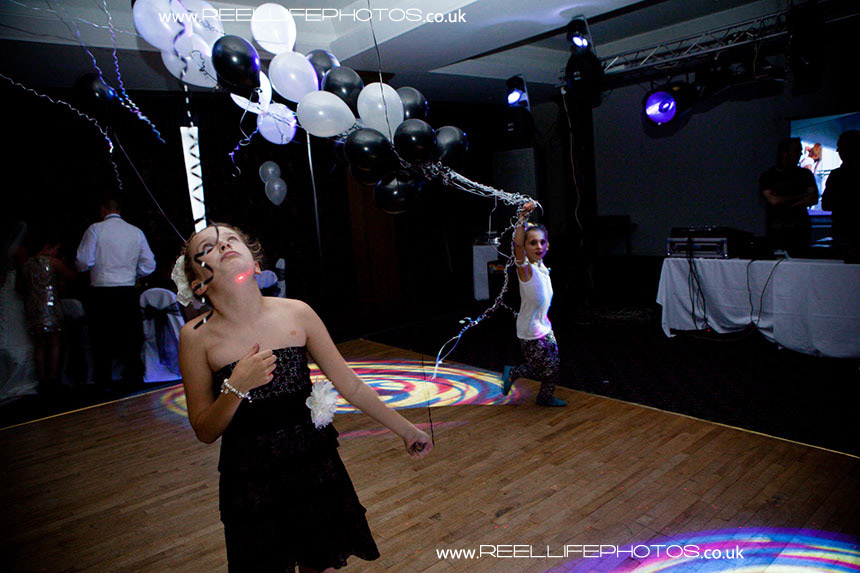 Evening wedding reception pictures with young girls dancing with balloons