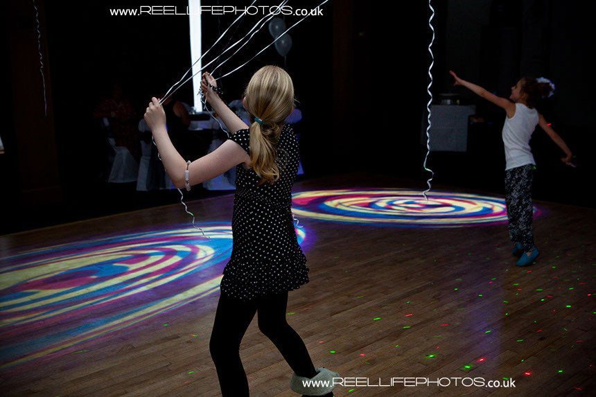 Evening wedding reception pictures with girls chasing balloons in DJ lighting