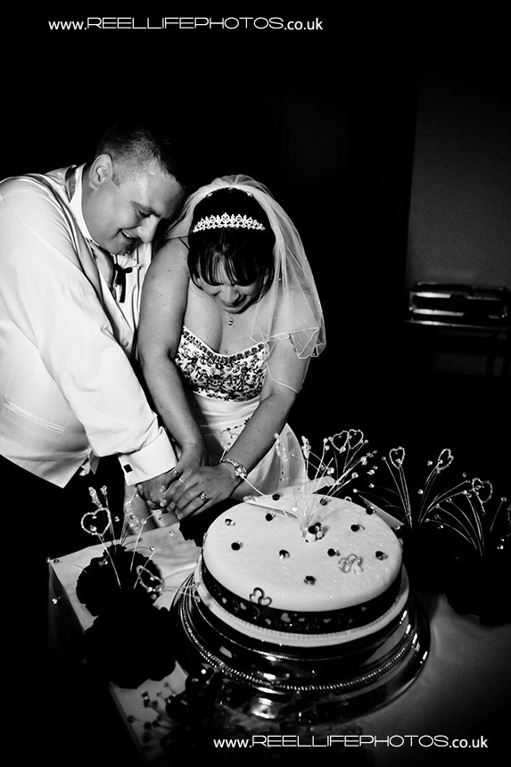 Cutting the cake at evening wedding reception