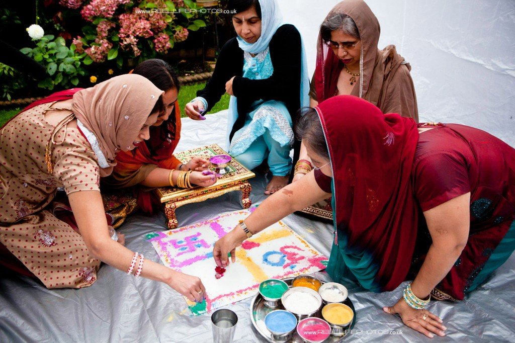 Hindu women put the finishing touches to their artwork for the Mayan wedding ceremony