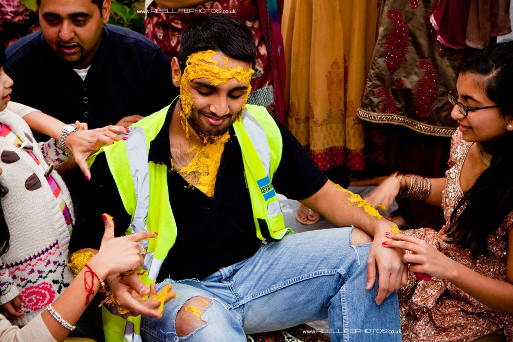 Hindu wedding ritual of painting the groom with yellow turmeric paste
