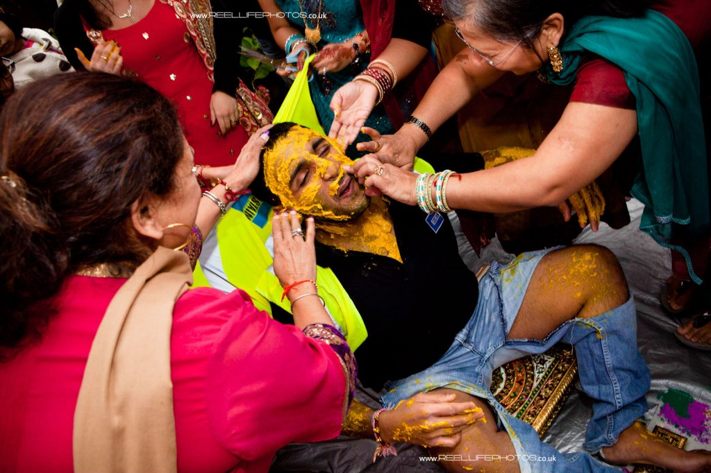 Hindu groom is smeared in yellow turmeric paste at his first wedding ceremony ritual