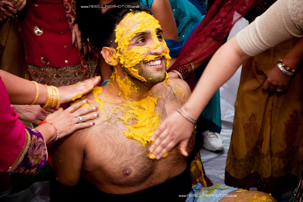 Groom gets stripped off to allow more turmeric paste to be rubbed onto his bare skin