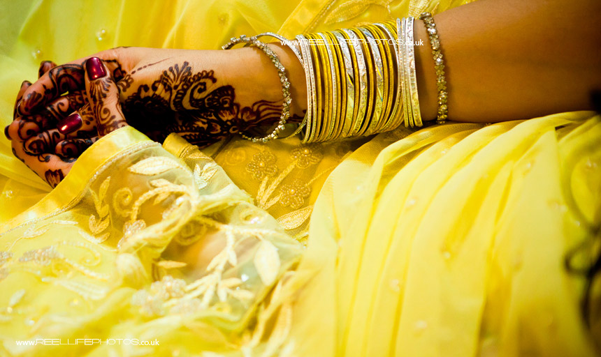 yellow sari with mehndi at Hindu wedding Sainth prayer ceremony