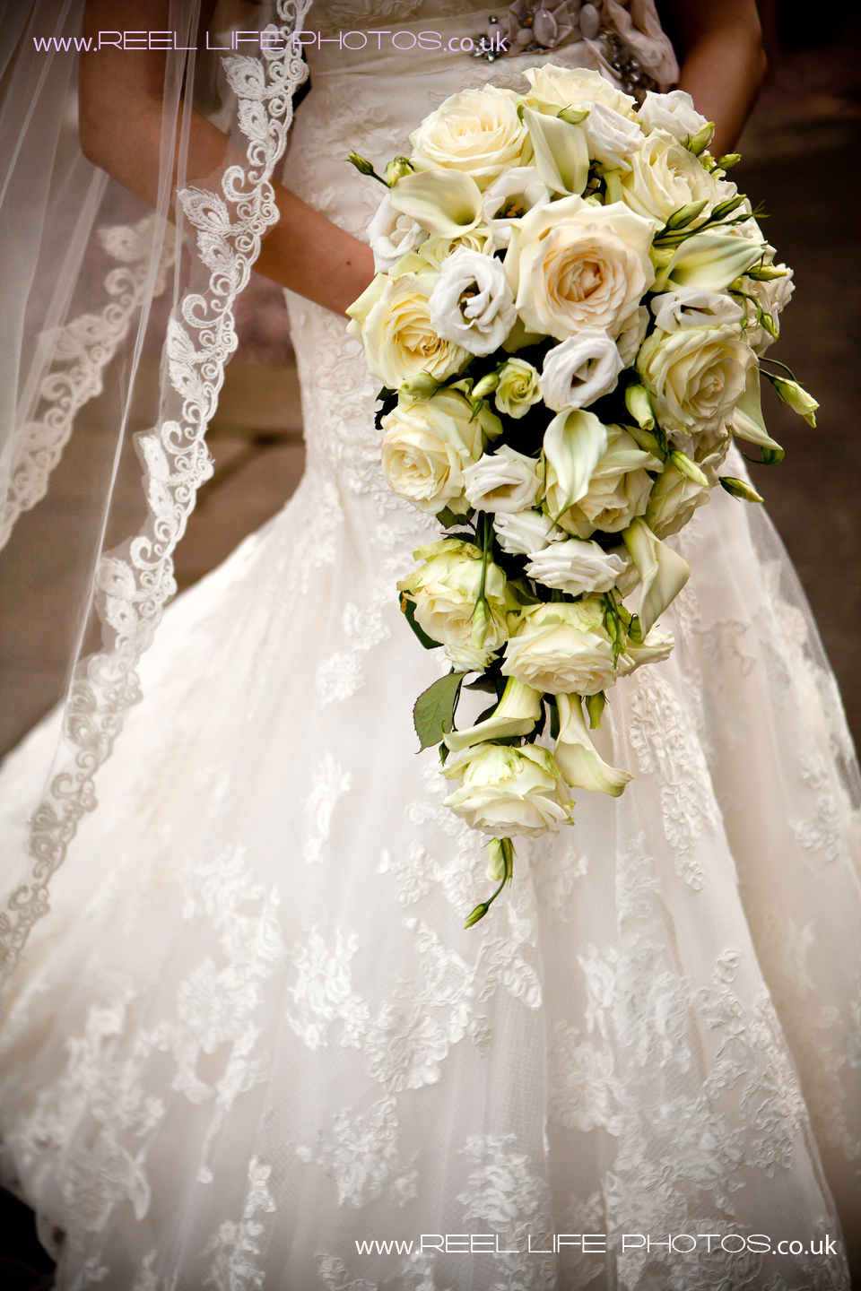 white wedding dress with lace and bouquet of yellow roses