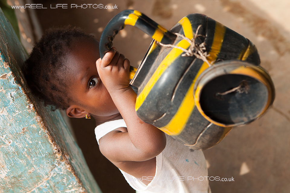 Cute Gambian child drinking water
